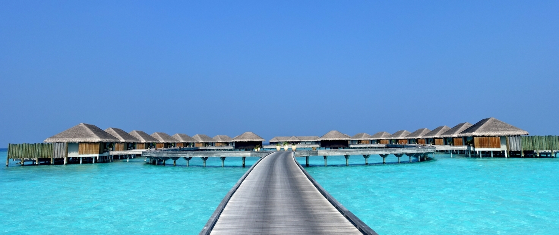 Holzsteg welcher zu 20 Wasservillen einer Luxus Privatinsel auf den Malediven führt